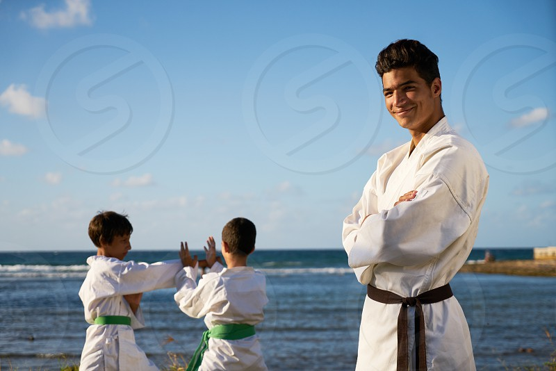 Teacher training children in karate and traditional martial arts. Simulation of fight near the sea. Portrait of instructor with boys in background photo