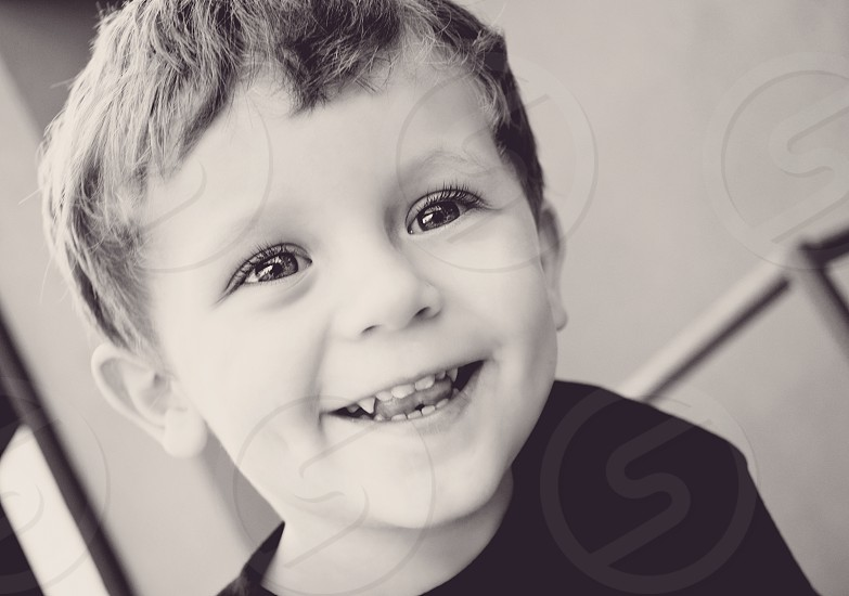 photo of a young child smiling with a captivating facial expression photo