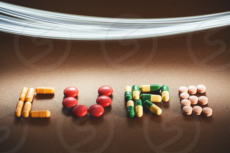 Word cure written with various different pills and tablets lighting effect in upper side of image.  photo