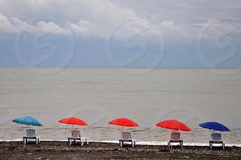 red patio umbrella beside seashore during daytime photo