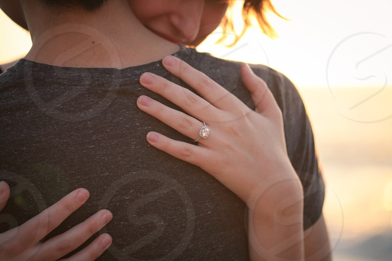 woman in solitary diamond silver ring hugging person in brown t shirt photo