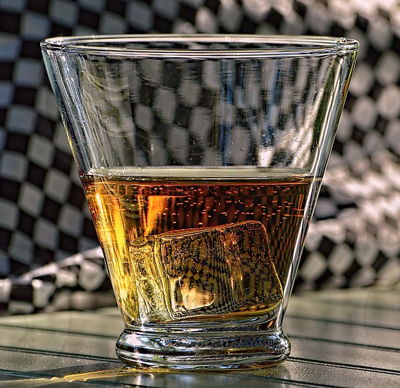 Glass of whiskey on ice with the racing finishing flag background photo