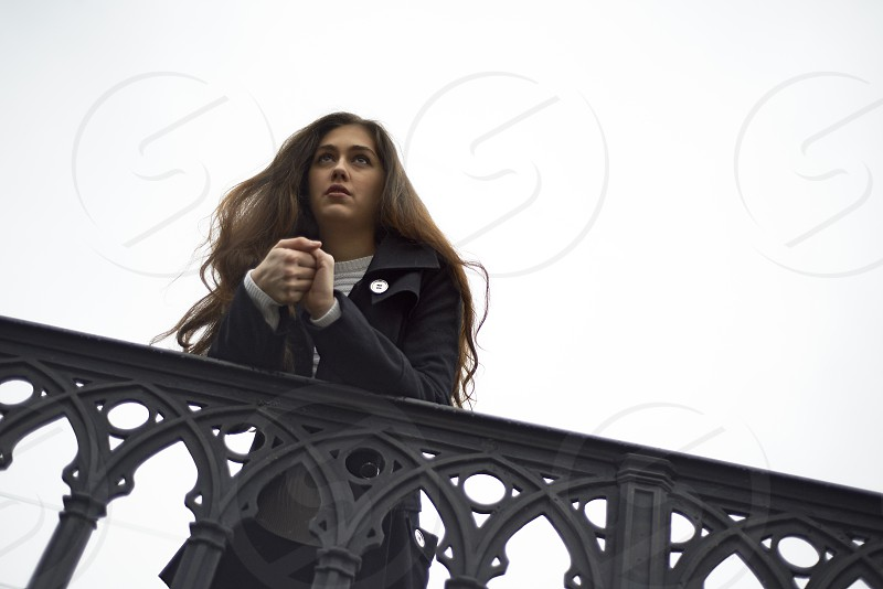 Bautiful young woman standing on a bridge in Zurich city centre looking out onto the water and talking on her mobile phone photo
