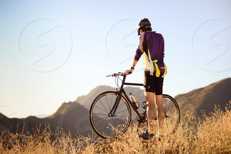 figure in purple shirt black spandex shorts standing with bicycle on top of hill photo