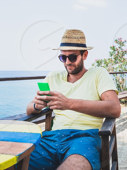 Young man using a smartphone on the terrace by the sea photo