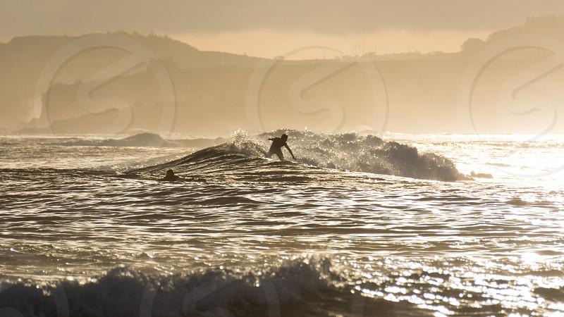 surfer surfing gold golden wave mountains splash water reflection bronze light photo