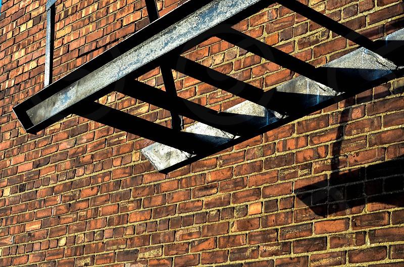 steel ladder beside brick wall photo