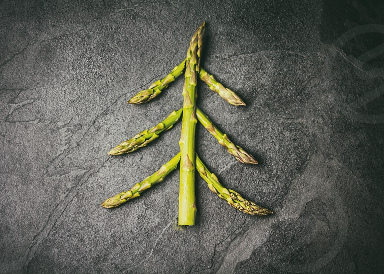 Christmas Food background. Christmas tree made from fresh asparagus on black stone slate background. Healthy holiday food vegan vegetarian and diet concept photo
