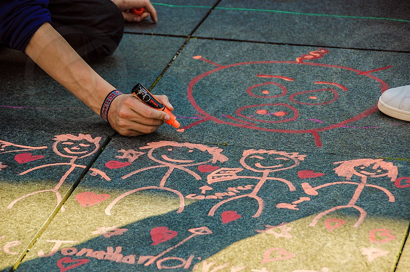 A teenager drawing art on the pavement. photo