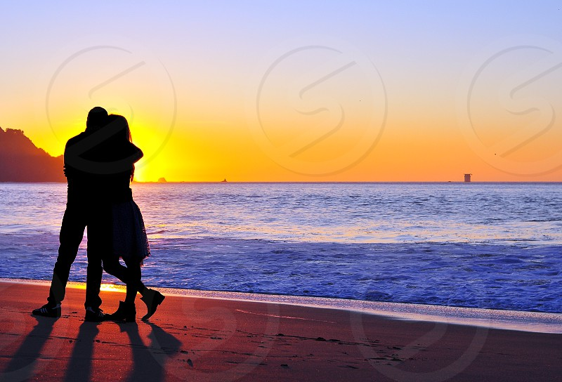 young people hugging in front of a sunset at baker beach san francisco photo