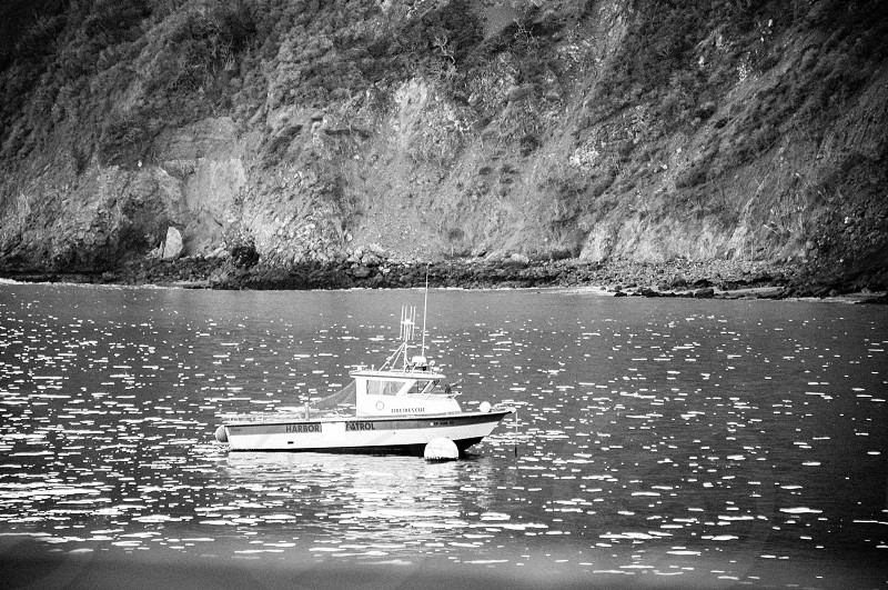 boat anchored in a cove on the ocean photo