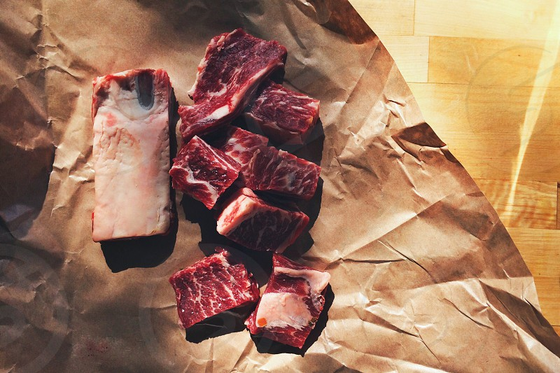 short rib pieces on parchment paper in warm light photo