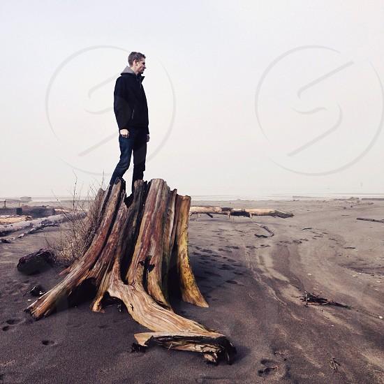man standing on a tree stump photo