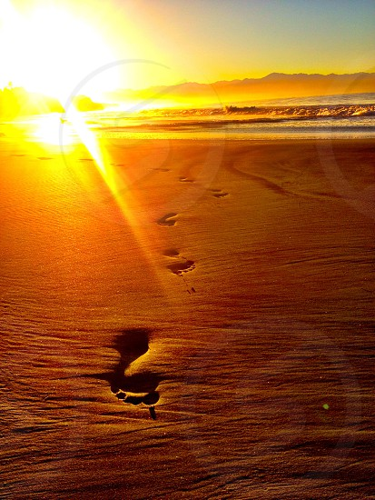 footprints on a beach at sunrise photo