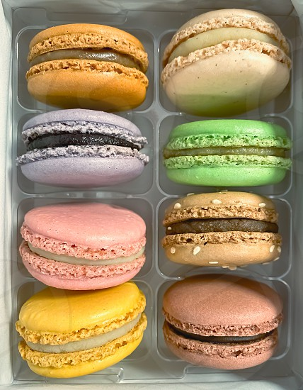 a group of colorful macarons stacked in a plastic package. Meringue-based dessert photo