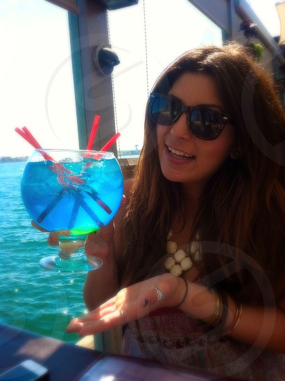 woman in black framed sunglasses holding a big short stemmed glass photo