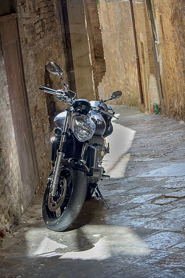 Motorcycle parked in the alleyway of Tuscany in the summer.  photo