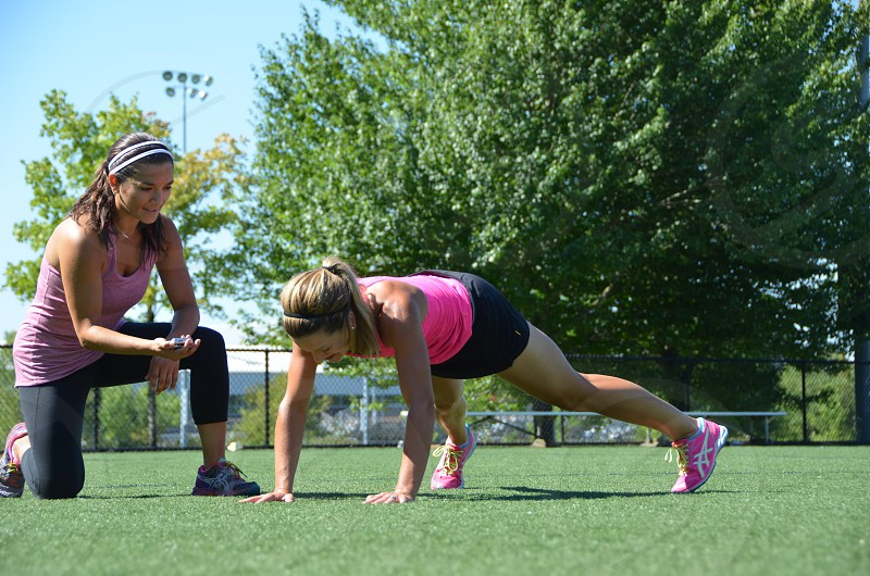 Female personal trainer with female client outdoors photo