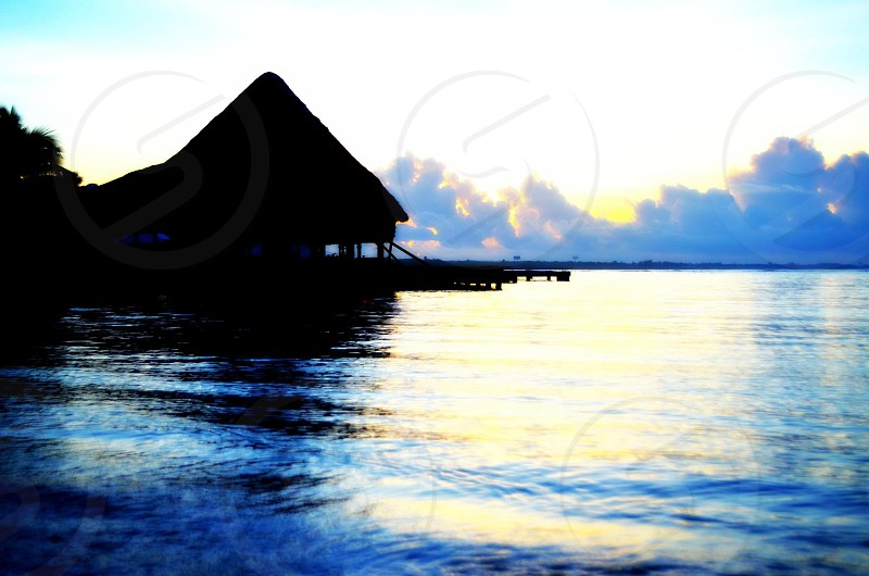 silhouette of house surrounded by water during daytime photo