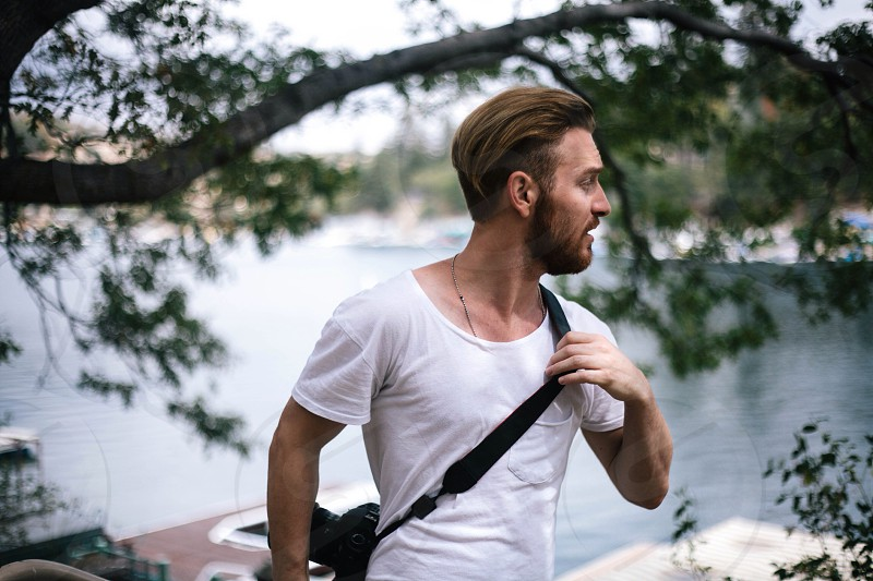 man in white scoop neckline t shirt with black sling bag photo