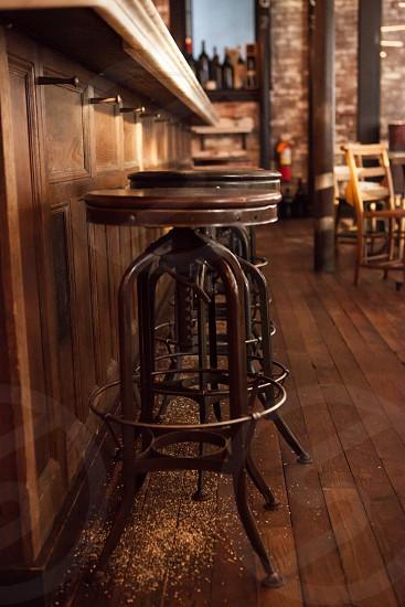 closeup photography of a brown wooden stool near bar counter photo