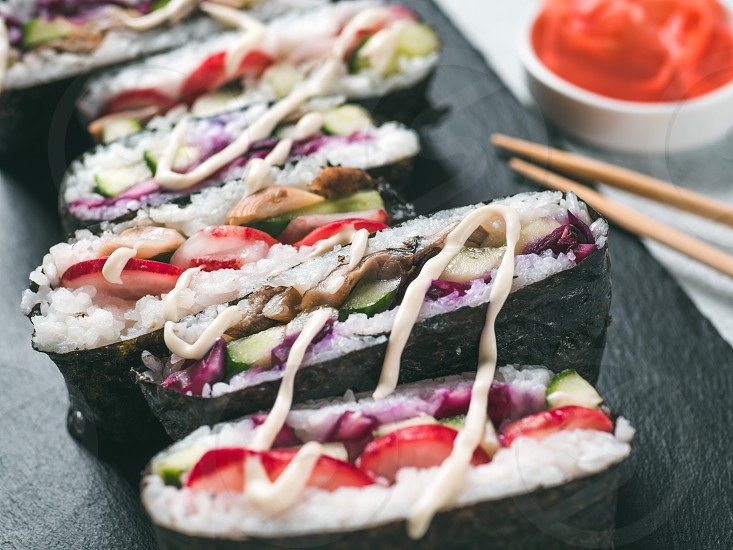 Vegan sushi sandwich onigirazu with vegetables. Healthy dinner recipe and idea. Colorful japan sandwich onigirazu with red cabbage radish cucumber mushrooms. Trend food. Close up shallow DOF photo