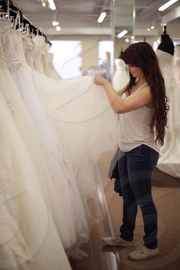 woman wearing white tank top and picking white gown photo
