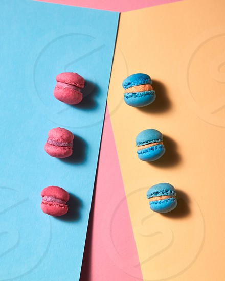 Blue and pink macaroons with reflection of shadows on a multicolored paper background. French dessert. Flat lay photo