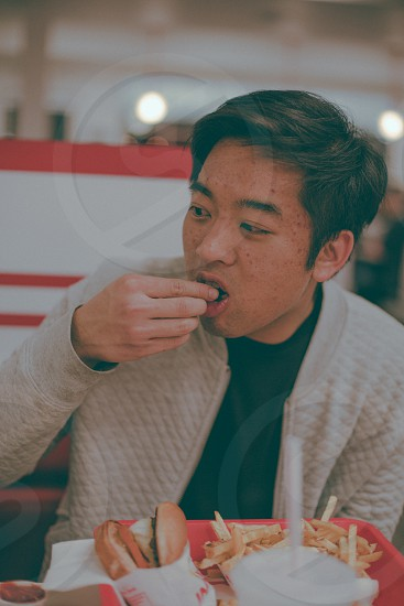 man wearing white jacket sitting and eating at restaurant table photo