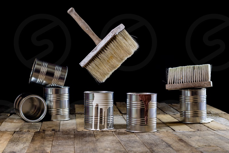 can of paint and brush hanging in the air. Paint brush and paint cans on a wooden table. Painting workshop. Black background photo