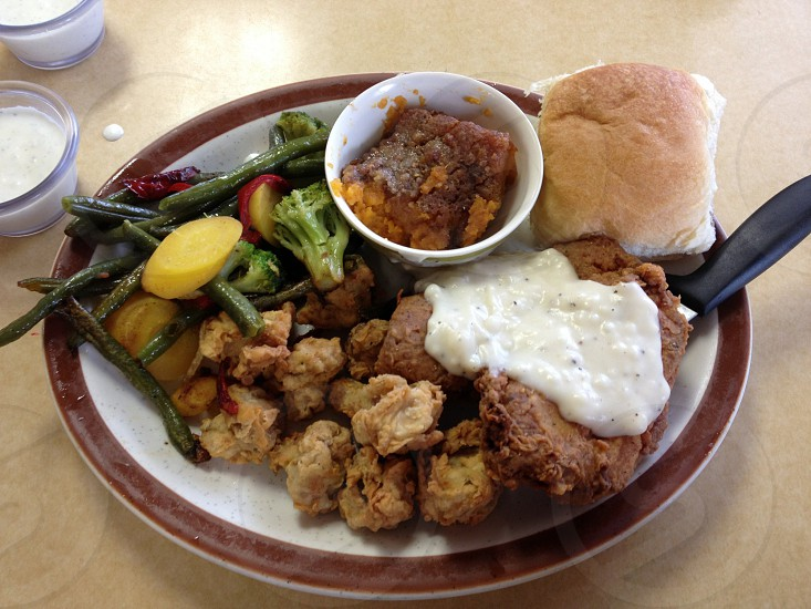 Chicken fried steak dinner with fried okra mixed veggies sweet potato casserole and roll lunch photo