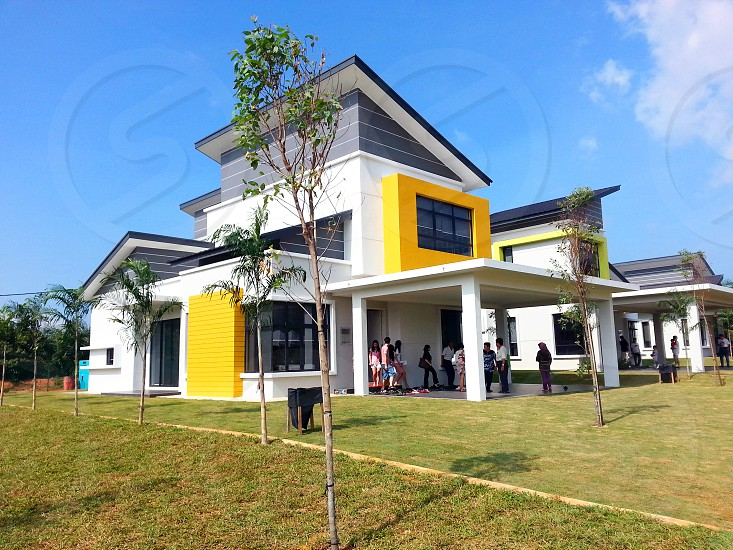 white yellow and black 3 tier house with people gathering inside with green grass field trimmed well and green leaf trees on outside photo