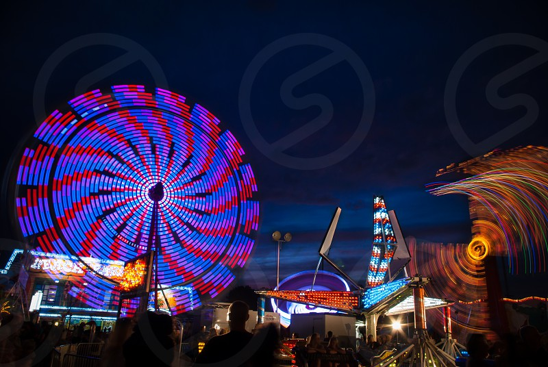 Long exporsure at the fair. Lights and people walking about the nigh.  photo