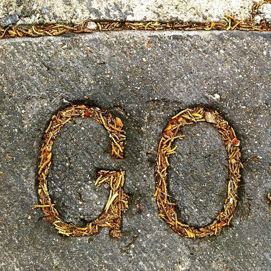 GO shaped sign on concrete pavement photo