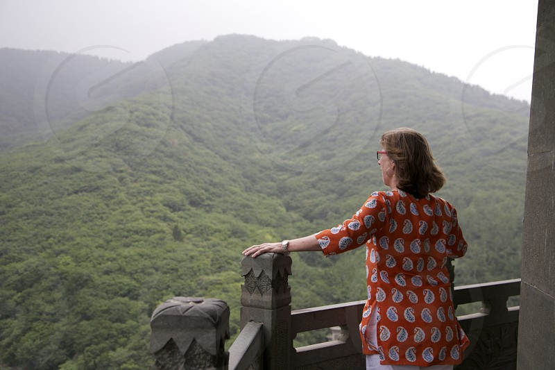 woman in orange and white paisley print blouse standing on balcony overlooking green tree covered mountain under light grey sky photo