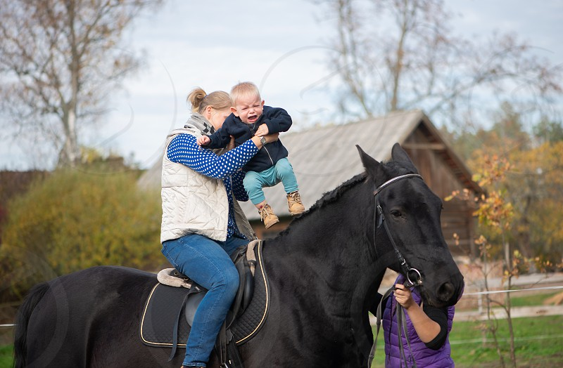A toddler together with his mother rides a horse for the first time in his life. photo