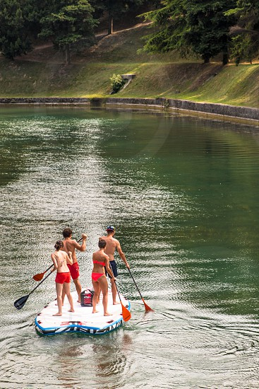 Couples Rafting At The Lake Park On Vacation In Summertime photo