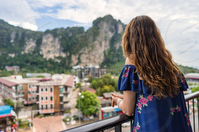 Young woman is standing on balcony in hotel in tropical country and look forward on big cliff and street. Rear view on female. photo