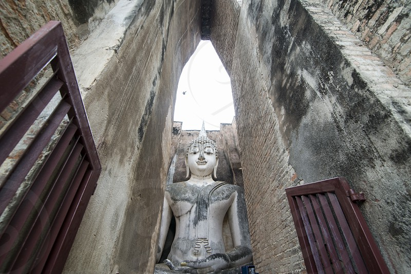 the Buddha at the Wat Si Chum at the Historical Park in Sukhothai in the Provinz Sukhothai in Thailand.   Thailand Sukhothai November 2018 photo