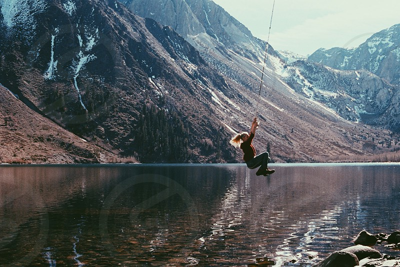 woman with ponytail swinging from rope over still lake in front of mountains photo