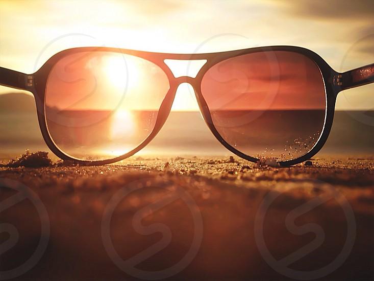 black framed sunglasses on sand surface photo