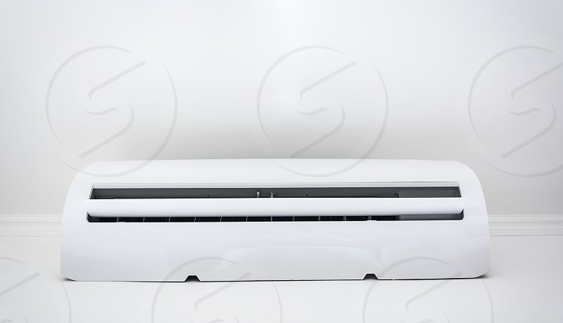Close up of white air conditioner swing mounted on a white wall photo