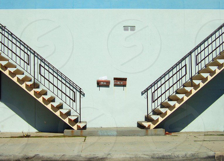 Double staircases are againsty a wall outdoors on a city sidewalk photo