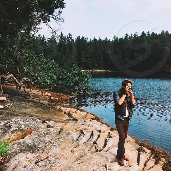 man taking photo on lake photo