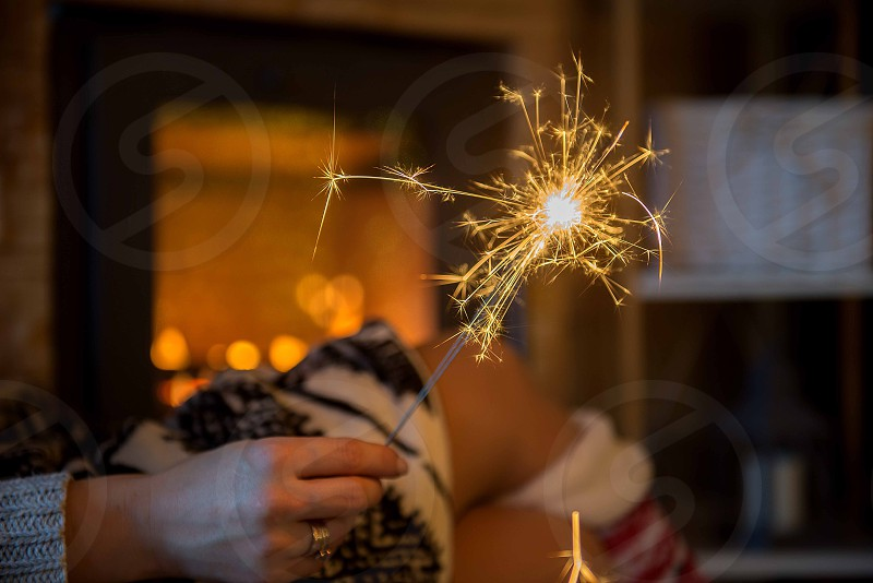 Young adult beautiful woman holding sparkler by fireplace in cozy mountain cabin photo