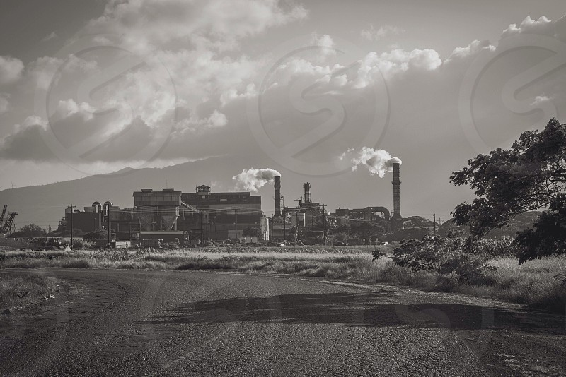black white photograph of mill with plumes of smoke beneath cloudy sky photo