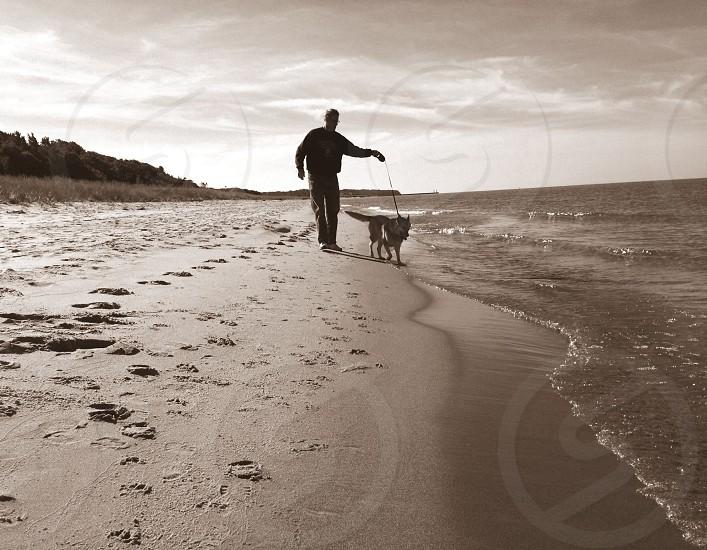Man walking a dog on Lake Michigan beach photo