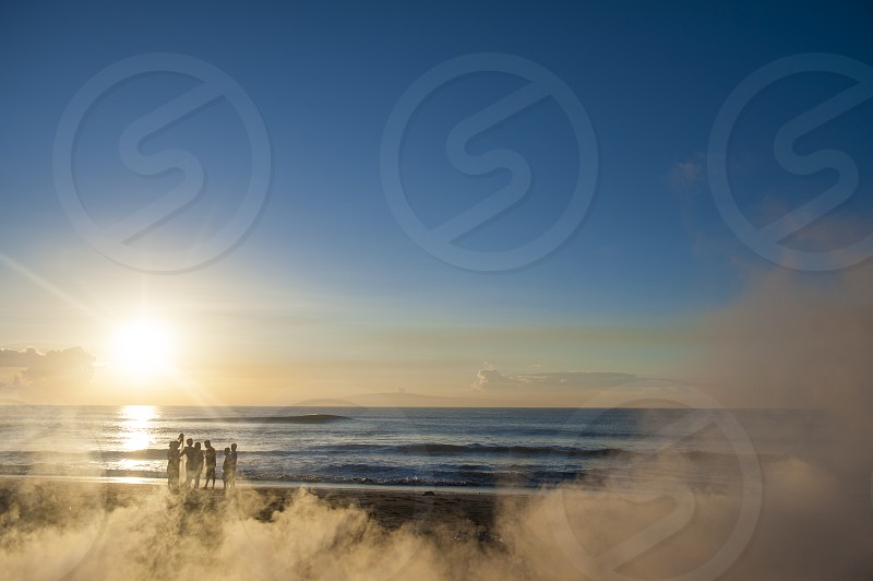 People standing on Balinese beach with smoke at sunrise photo