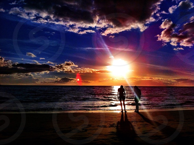 couple walking on a beach in a sunset photo