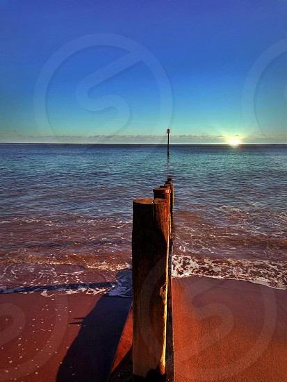 beach waves and wooden pole view ] photo